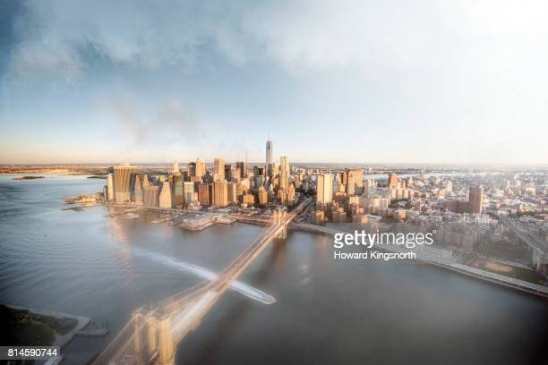 Aerial view of NYC, East River and Brooklyn Bridge with misty sky