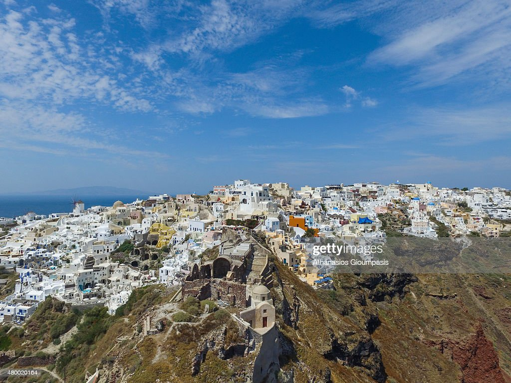 Aerial view of Oia town on June 30 2015 in Santorini GreeceOia typifies the white painted houses of the Cyclades built directly into niches which are...