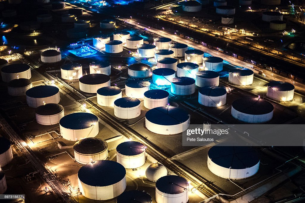 Aerial view of oil refinery storage tanks illuminated at night, Los Angeles, California, USA