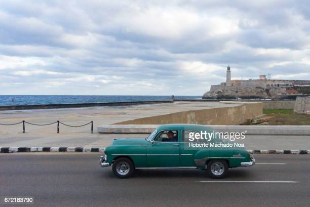 Aerial view of old vintage car with 'El Morro' colonial fortress in the background Everyday lifestyle in the Cuban capital city