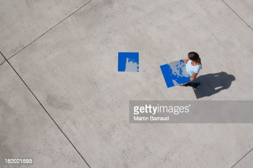 Aerial View of person with piece of world map puzzle outdoors : Stock Photo