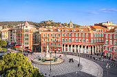 Aerial view of Place Massena square with red buildings  and fountain in Nice, France