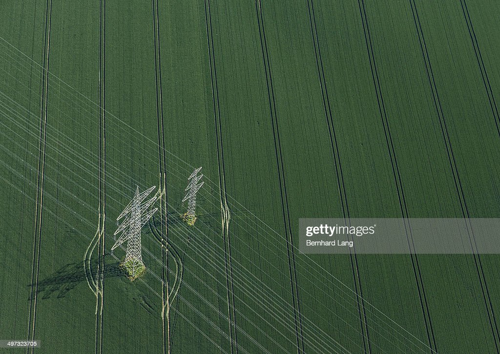 Aerial view of power poles on green field