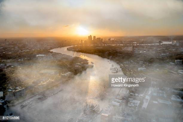 Aerial view of River Thames and city at sunrise with mist