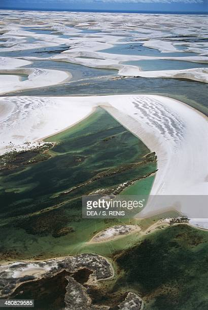 Aerial view of sand dunes known as 'bed sheets' and freshwater lakes with iridescent colours in Lencois Maranhenses National Park State of Maranhao...