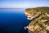 Aerial view of the awesome cliffs of Costa Brava with the blue sea. Tossa de Mar, Girona.