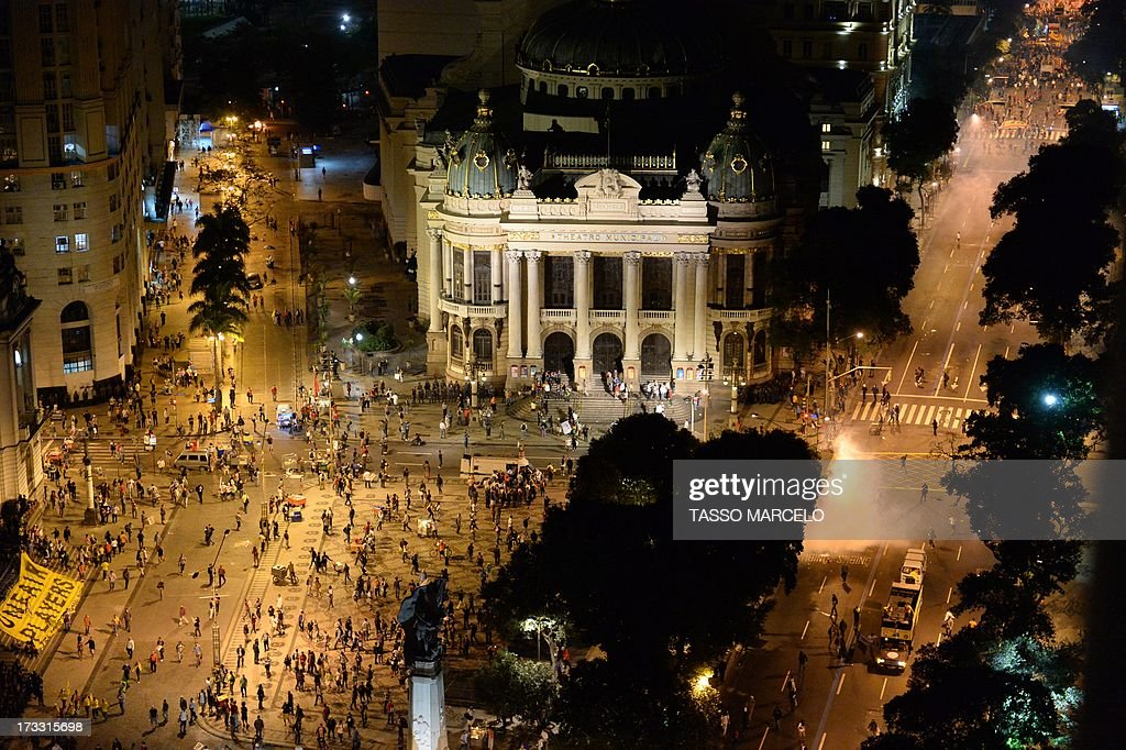 Aerial view of the clashes happening in front of the Municipal Theatre in Rio de Janeiro on July 11, 2013 after a march by Brazilian workers in a day of industrial action called by major unions to press demands for better work conditions. Demonstrators on Thursday blocked roads and staged protest rallies across the country on the 'National Day of Struggles' which was called by the country's five leading labour federations during last month's mass street protests to demand better public services and an end to endemic corruption. AFP PHOTO / TASSO MARCELO