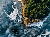 Aerial view of the winter snow covered forest and frozen lake from above captured with a drone in Finland.