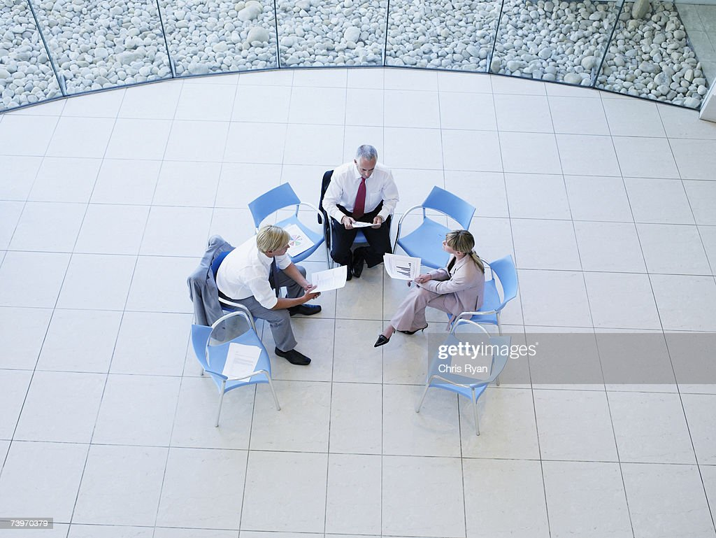 Aerial view of three office workers meeting in a rotunda : Stock Photo