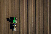 Aerial view of tractor driving over bare dirt