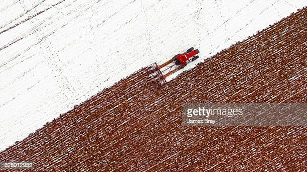 Aerial view of tractor tilling snow covered field in Winter