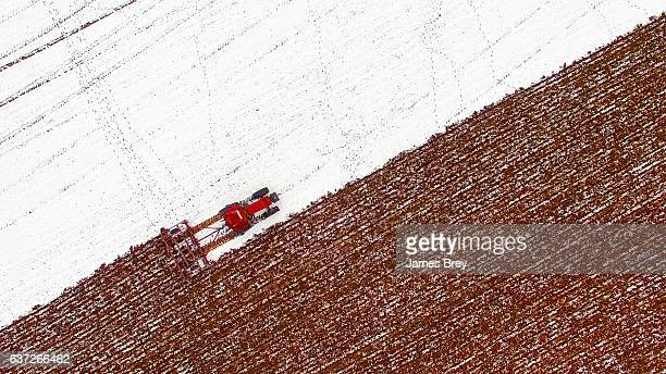 Aerial view of tractor tilling snow covered field
