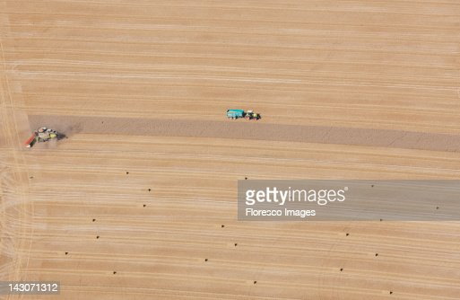 Aerial view of tractors at work in crop fields : Stock Photo