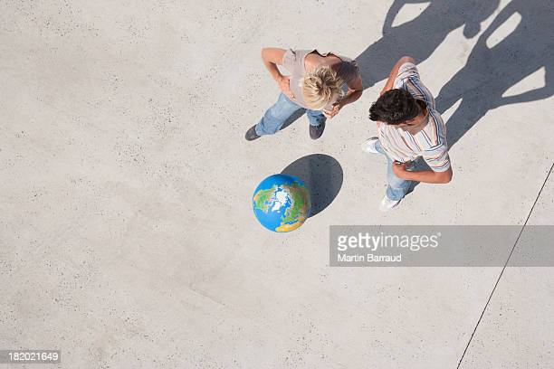 Aerial View of two people looking at globe