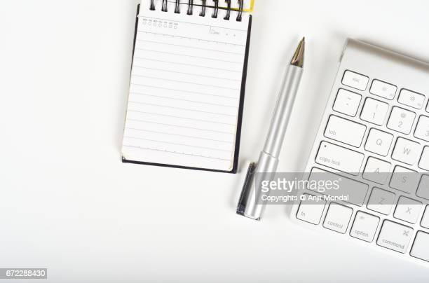 Aerial View of White Background Office Desk with Notepad, pen and Computer Keyboard