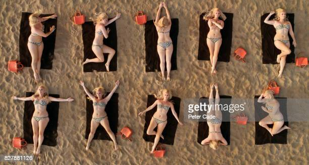 Aerial view of woman sunbathing on beach in different positions