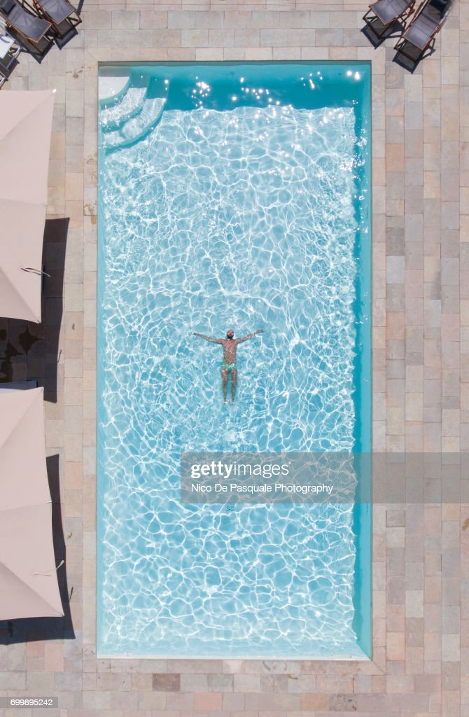 aerial view of young man into swimming pool stock photo