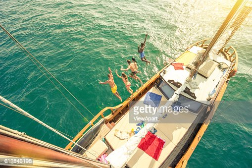 Aerial view of young people jumping from sailboat sea trip : Foto de stock