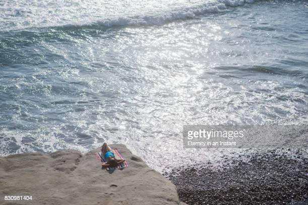 Aerial View of Young woman sunbathing by the sea