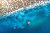 Aerial view of young woman swimming on the pink swim ring in the transparent turquoise sea in Oludeniz,Turkey. Summer seascape with girl, beautiful waves, blue water at sunset. Top view from drone