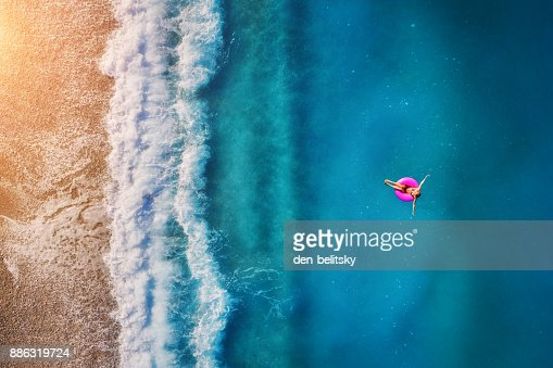 Aerial view of young woman swimming on the pink swim ring in the transparent turquoise sea in Oludeniz. Summer seascape with girl, beach, beautiful waves, blue water at sunset. Top view from drone : Stock Photo