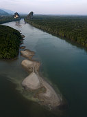 Image from drone of river in Krabi town, Thailand. Green trees, mountains and rocks around river.