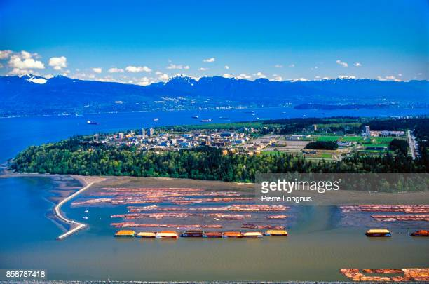 Aerial View on the Fraser Delta and Timber raft with the University of British Columbia and the Coast Mountain Range in the Background - Vancouver, British Columbia, Canada