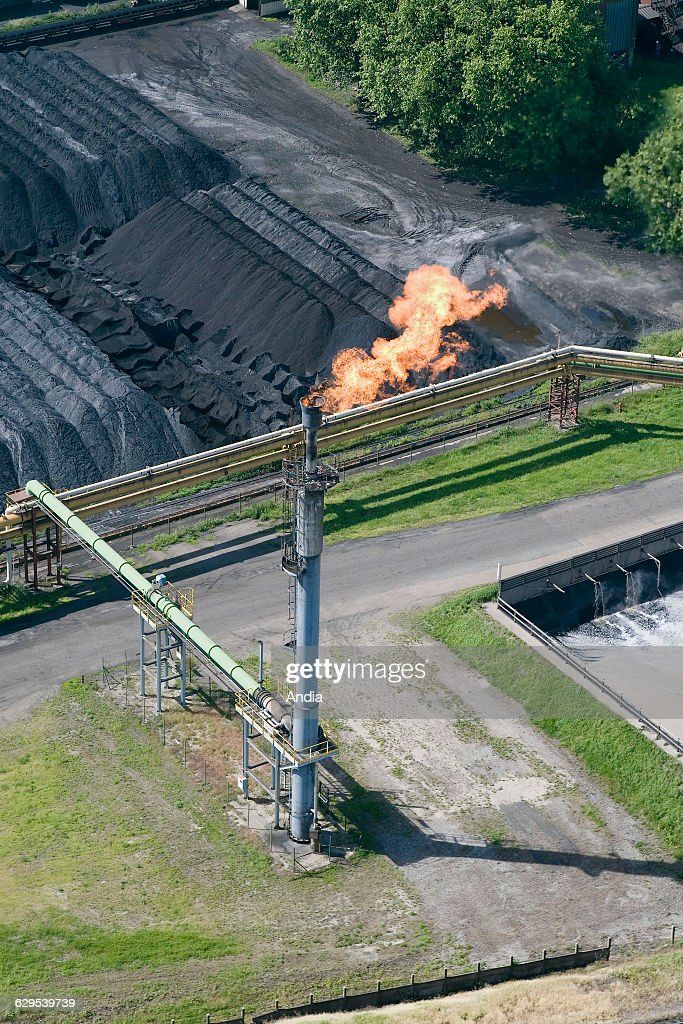 Aerial view over a flare pit next to a coal heap