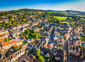 Aerial view over the iconic Cotswold village of Painswick, with its honey coloured limestone cottages deep in the bucolic countryside of Gloucestershire, UK, framed by vibrant green patchwork fields a
