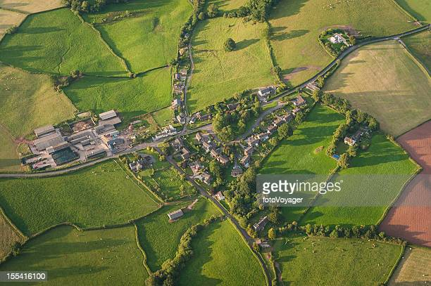 Aerial view over tranquil country village and summer farmland