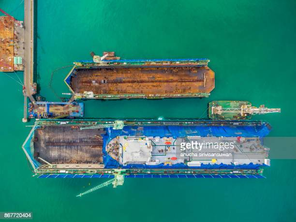 aerial view shipyard have crane machine and container ship in green sea .
