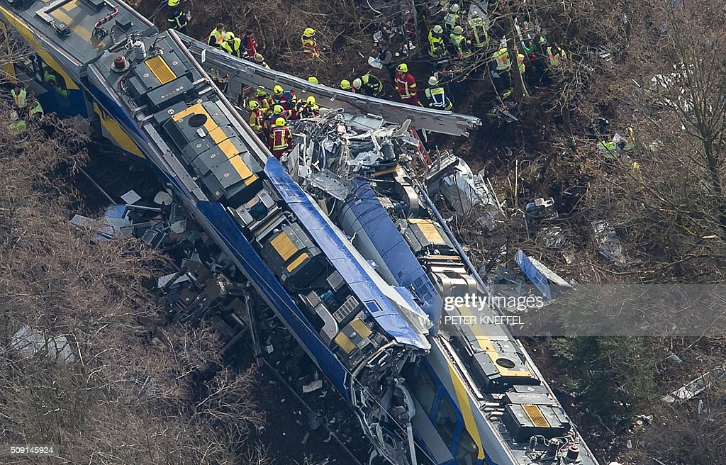 Aerial view shows firefighters and emergency doctors working at the site of a train accident near Bad Aibling, southern Germany, on February 9, 2016. Two Meridian commuter trains operated by Transdev collided head-on near Bad Aibling, around 60 kilometres (40 miles) southeast of Munich, killing at least eight people and injuring around 100, police said. The cause of the accident was not immediately clear. / AFP / dpa / Peter Kneffel / Germany OUT