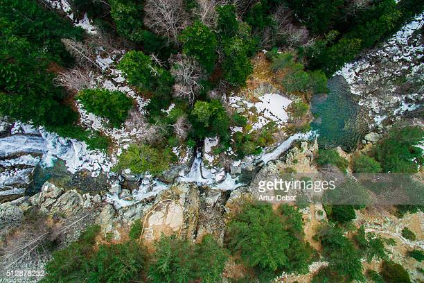 Aerial view taken by drone of the snowy Aiguestortes National Park waterfalls on winter with beautiful green pools and forest in the Catalan Pyrenees.