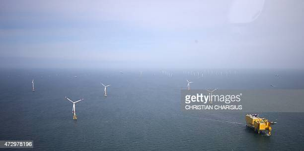Aerial view taken on May 11 2015 shows windmills of the 'Nordsee Ost' wind park and the HelWin alpha and HelWin beta converter platform off the coast...