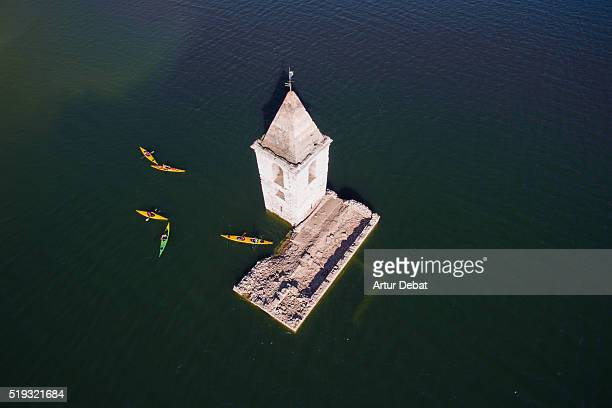 Aerial view taken with drone of people practicing Kayaking with the emergent church submerged into the waters of the Sau reservoir in the Catalonia region.