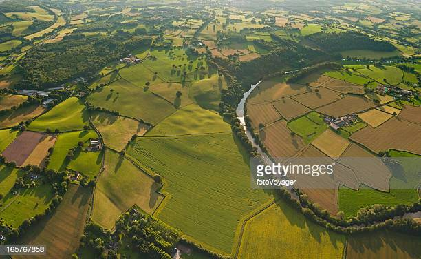 Aerial vista over patchwork green fields idyllic rural landscape