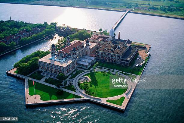 Aerial wide shot of Ellis Island with the sun reflecting in the water.