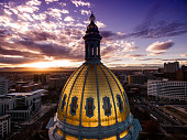 Beautiful drone photograph of a sunset over the golden cupola of the Colorado Capital building in the city of Denver