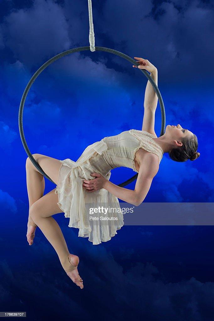 Aerialist performing on hoop against blue background