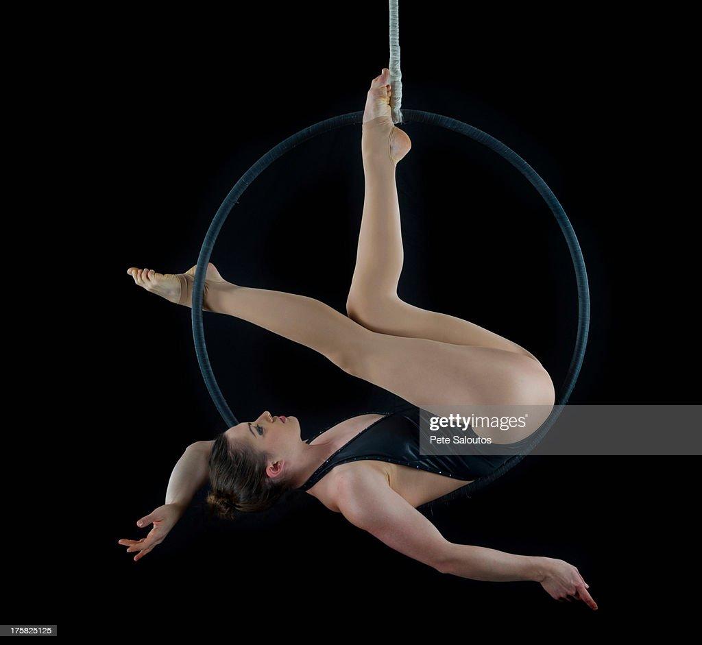 Aerialist performing on hoop in front of black background