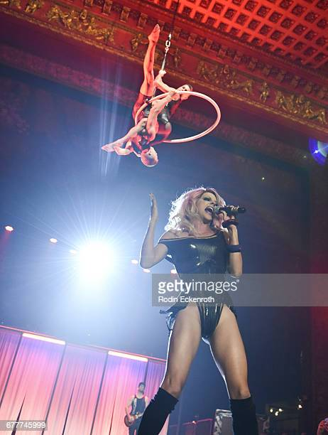 Aerialists Les Farfadais and musical artist Courtney Act perform during MARCO MARCO presents 'A Night In The Red Light' Fashion Show at Globe Theatre...