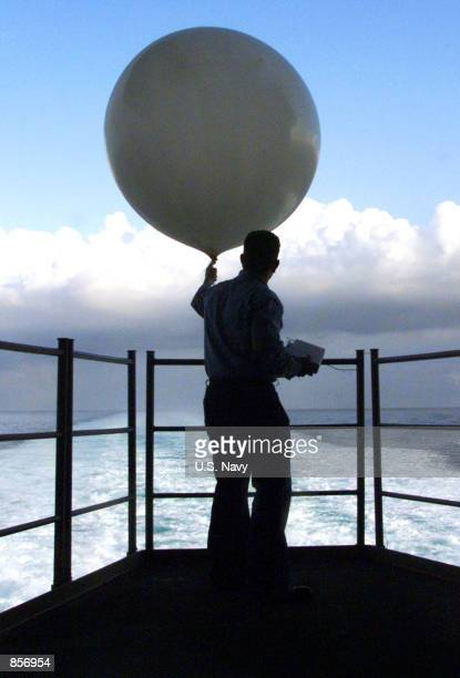 Aerographers Mate 3rd Class Robert Mason of Chicago IL releases a weather balloon from the fantail of the USS Harry S Truman September 26 1999...