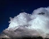 Aeroplane flying near large cloud