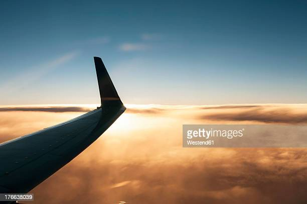Aeroplane wing above cloud at sunset