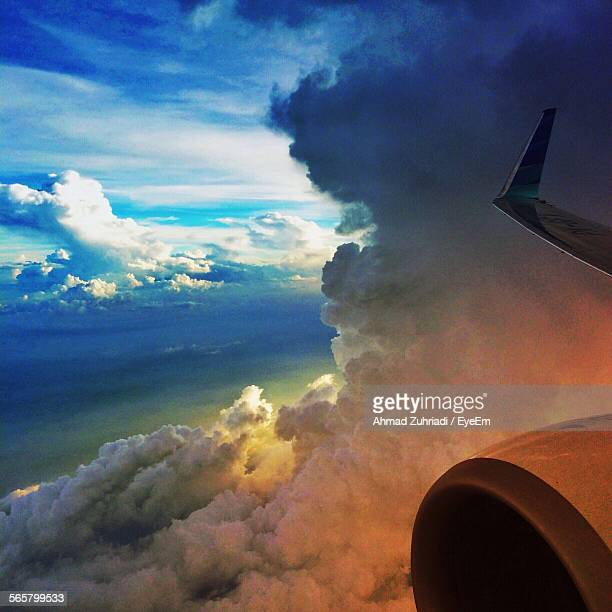 Aeroplane Wing Amidst Clouds During Sunset