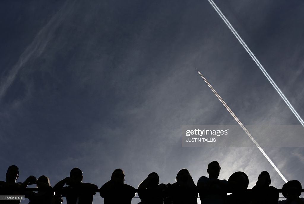 Aeroplanes leave trails in the sky as spectators watch Bulgaria's Tsvetana Pironkova play against Switzerland's Belinda Bencic during their women's singles first round match on day one of the 2015 Wimbledon Championships at The All England Tennis Club in Wimbledon, southwest London, on June 29, 2015. RESTRICTED