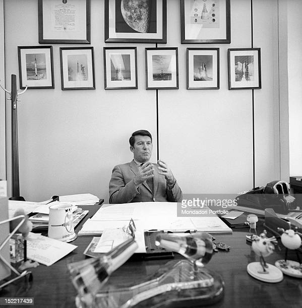 Aerospace engineer in his office by NASA Behind him photos of some missions