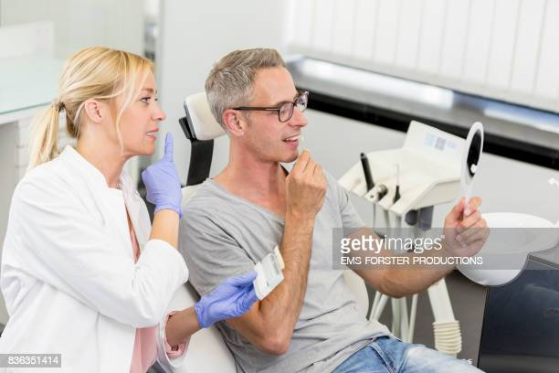 aesthetic dentistry dentist's office - female doctor dentist in her late 30s with long blonde hair in doctor's white coat medical scrubs and exam gloves discussing the dental care whitening bleaching process with male patient using a tooth color chart.