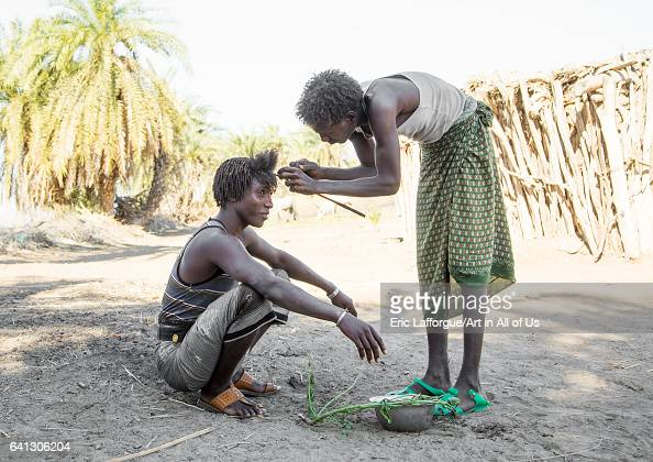 Afar man having a traditional hairstyle with a stick to make curly hair on January 15 2017 in Afambo Ethiopia