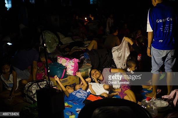 Affected families take shelter in a gymnasium converted into an evacuation center after continued monsoon rains triggered by tropical storm FungWong...